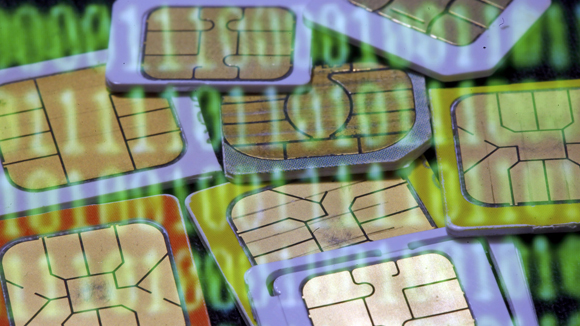 SIM cards are reflected on a monitor showing binary digits in this photo illustration taken in Sarajevo